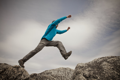 A hiker leaps between two granite rocks on the summit of Needle Peak, BC, Canada.