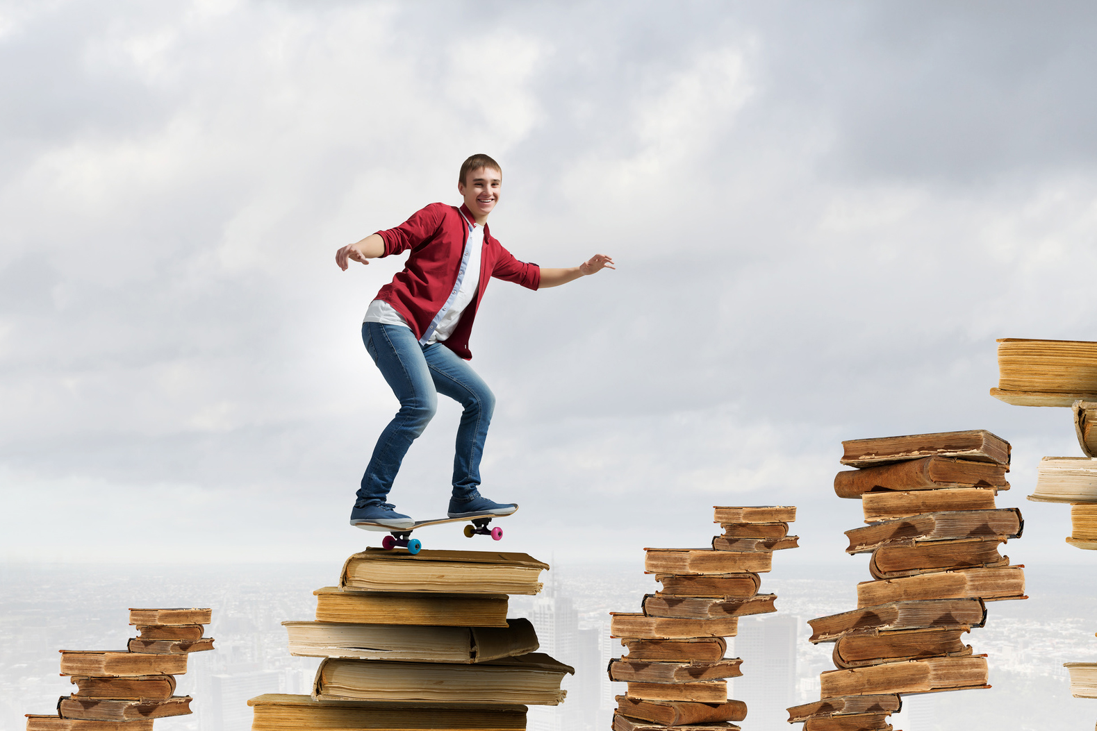 Handsome teenager acive boy riding skateboard on books