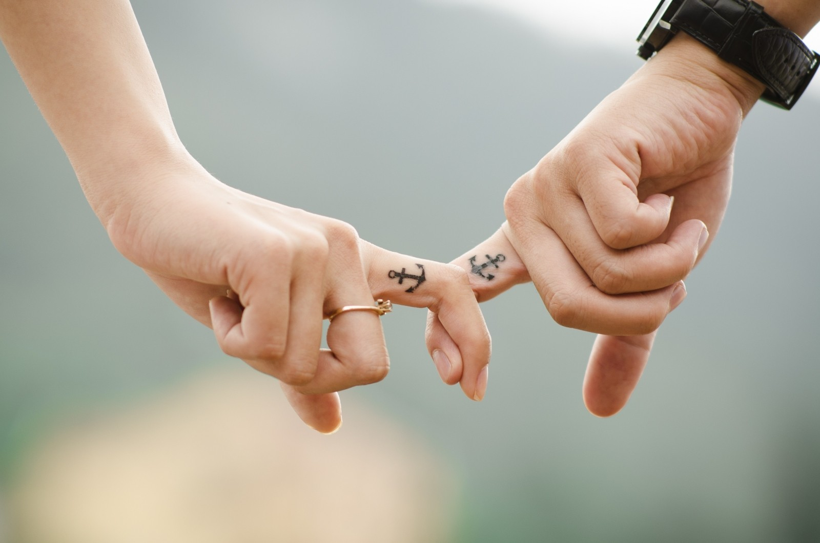 1-young-couple-holding-hands-with-tatoos-on-fingers