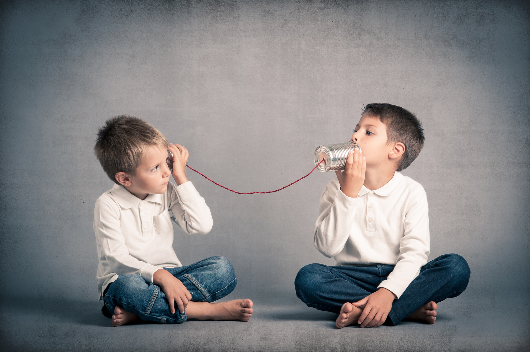 Young brothers talking with tin can telephone