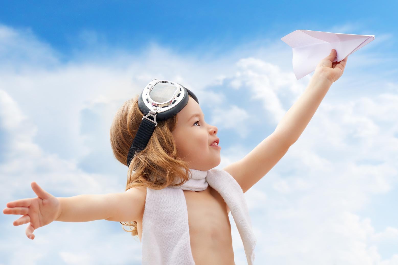A child plays an airplane pilot