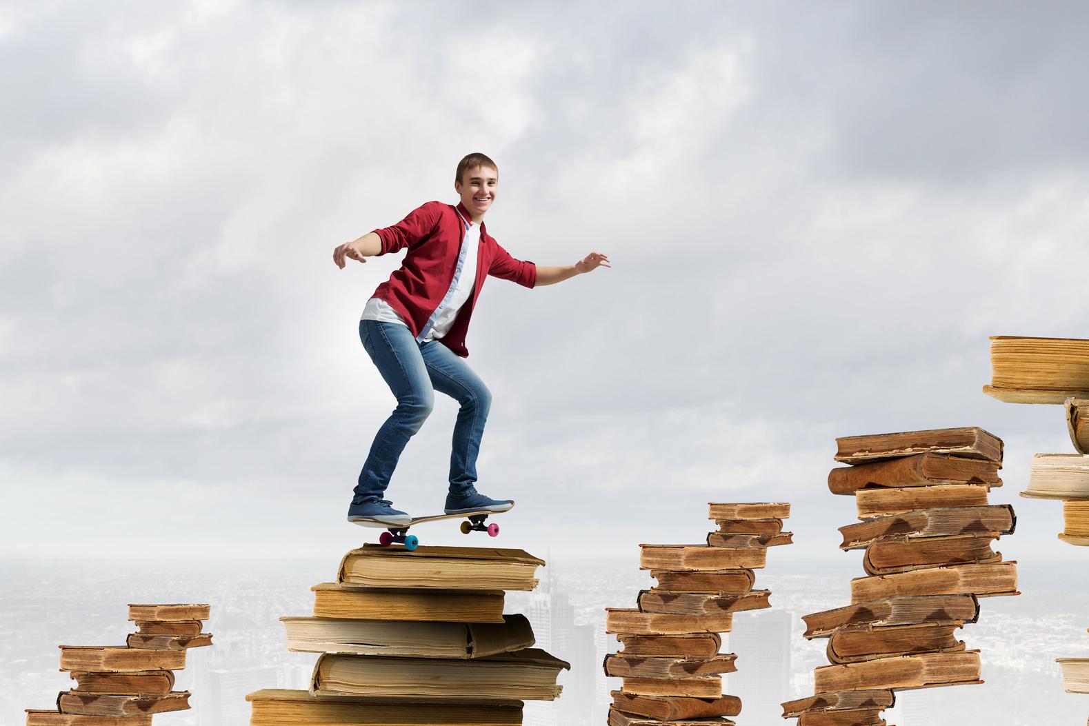 Handsome teenager acive boy riding skateboard on books