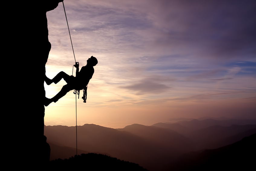 Silhouette of a climber on a vertical wall over beautiful sunset